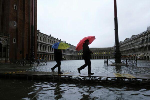Die Vorhalle des Markusdoms wurde völlig überschwemmt. Dem Aufseher zufolge ist eine kritische Situation entstanden. Vor einem Jahr war das Wasser sogar in die Innenräume eingedrungen, wobei das Mosaik und die Säulen beschädigt wurden. Foto: Menschen auf dem überschwemmten Markusplatz in Venedig.  - SNA