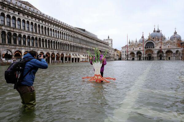 Diesmal ist die Situation glücklicherweise nicht so dramatisch, wie vor einem Jahr. Es wird erwartet, dass der Wasserspiegel auf 1,45 Meter steigen wird. Vor einem Jahr waren es 1,87 Meter. Foto: Menschen fotografieren sich auf dem überschwemmten Markusplatz in Venedig. - SNA