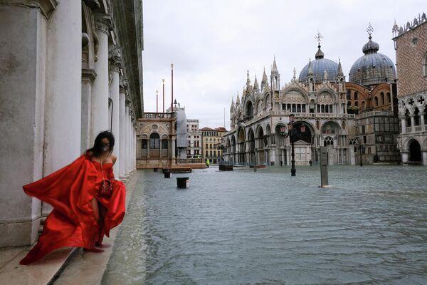 Ein Model auf dem überfluteten Markusplatz in Venedig. - SNA