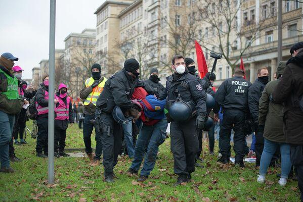 Polizisten führen einen Teilnehmer mit FDJ-Hemd ab. - SNA