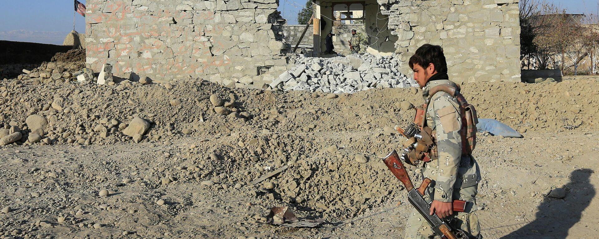 Ein afghanischer Polizist vor einem durch einen Bombenangriff zerstörten Gebäude im Distrikt Khogyani, Provinz Nangarhar . - SNA, 1920, 04.04.2021