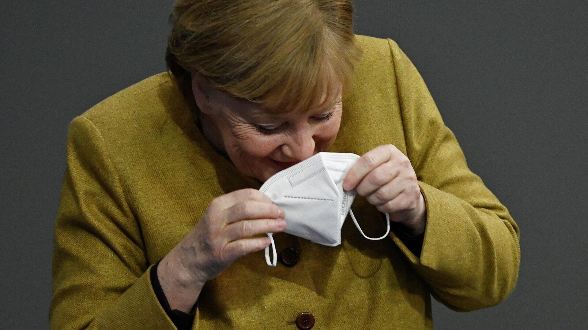 Bundeskanzlerin Angela Merkel lacht, nachdem sie ihre Gesichtsmaske auf dem Rednerpult im Bundestag vergessen hatte, den 11. Februar 2021 in Berlin. - SNA, 1920, 16.02.2021