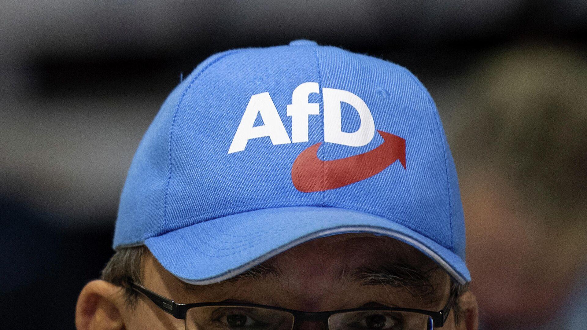 ein Teilnehmer einer Veranstaltung der Partei  AfD in der Sachsen Arena in Riesa trägt eine Mütze mit dem Logo der Partei. 13. Januar 2019. - SNA, 1920, 23.09.2021