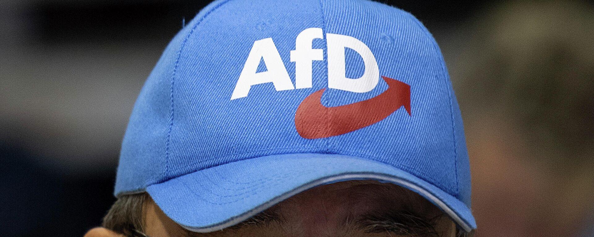 ein Teilnehmer einer Veranstaltung der Partei  AfD in der Sachsen Arena in Riesa trägt eine Mütze mit dem Logo der Partei. 13. Januar 2019. - SNA, 1920, 04.06.2021