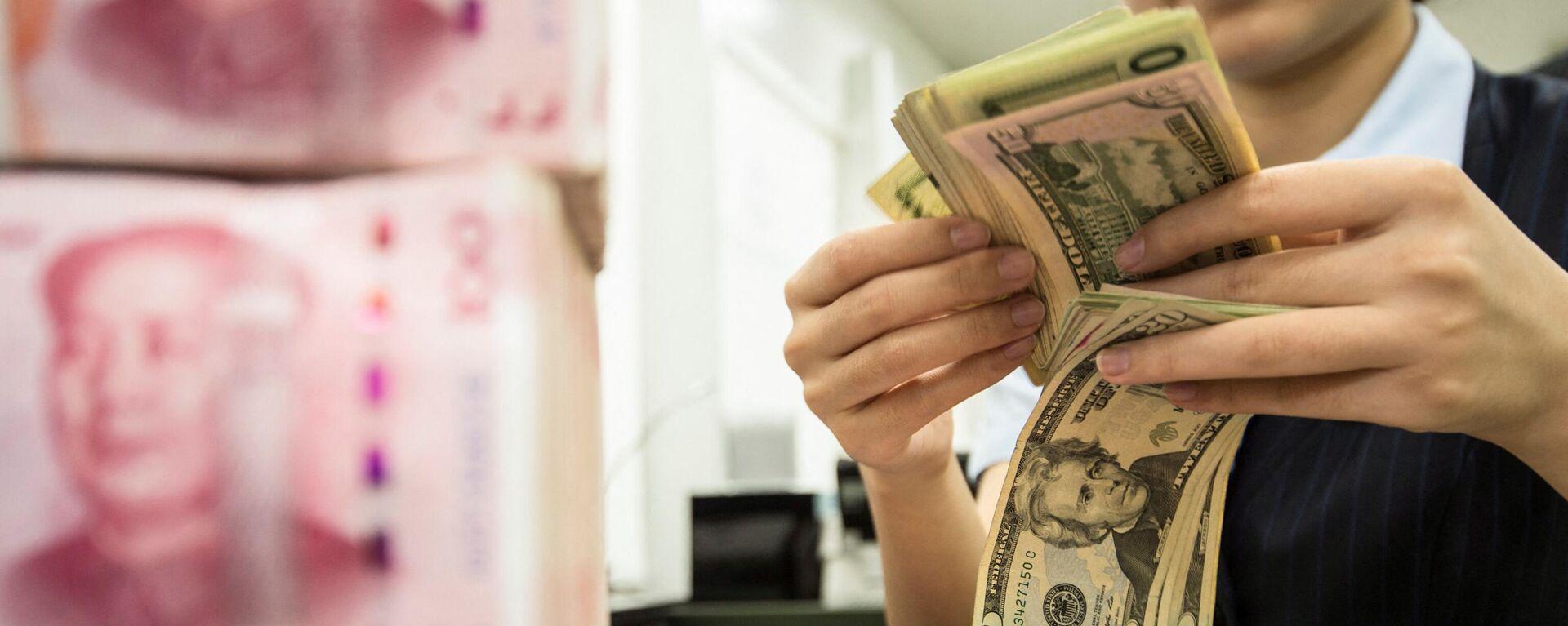Ein chinesischer Bankangestellter zählt an einem Bankschalter in Nantong in der östlichen chinesischen Provinz Jiangsu 100-Yuan-Banknoten und US-Dollar-Scheine, 6. August 2019. - SNA, 1920, 04.04.2021