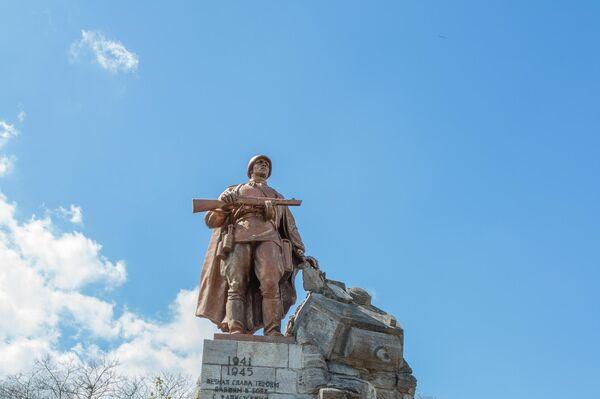"""Hinter der Tafel befindet  sich die Monumentalstatue auf der Anhöhe, die in nur fünf Monaten geschaffen und im November 1945 aufgestellt wurde. Die Inschrift lautet auf Deutsch: """"1941–1945 / Ewiger Ruhm den Helden, gefallen in den Kämpfen gegen die faschistischen Eindringlinge für die  Freiheit und Unabhängigkeit der Sowjetunion"""". - SNA"""