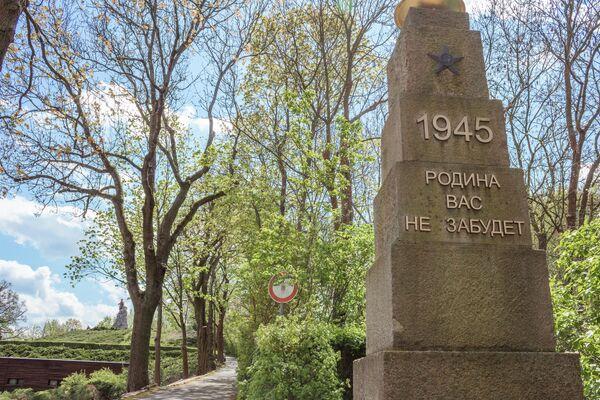 """Verlässt man das Gelände  entlang des Militärgeräts verabschiedet eine zweite Stele die Besucher mit Worten an ihre Gefallenen: """"1945 - Родина ваc не забудет"""", zu Deutsch: """"1945 – Die Heimat wird Euch nicht vergessen"""". - SNA"""