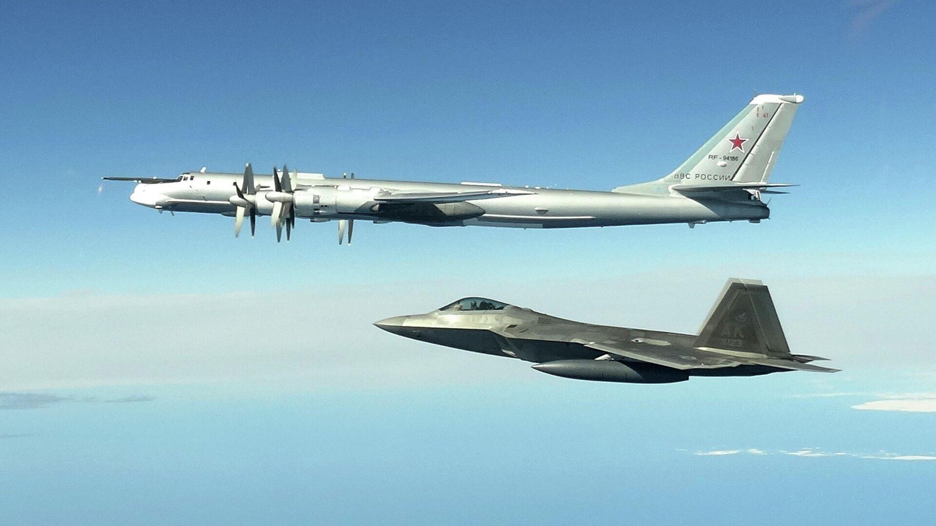 Ein russischer Tu-95-Bomber wird von einem US-amerikanischen F-22-Raptor-Jäger vor der Küste Alaskas abgefangen - SNA, 1920, 09.05.2021