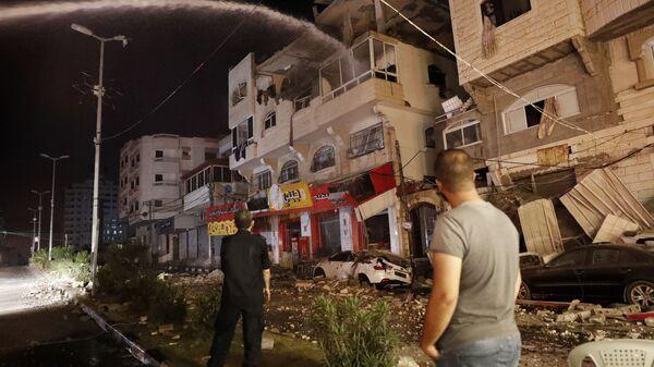Пожарные тушат горящие жилые дома после того, как они пострадали от израильских авиаударов, в городе Газа - SNA