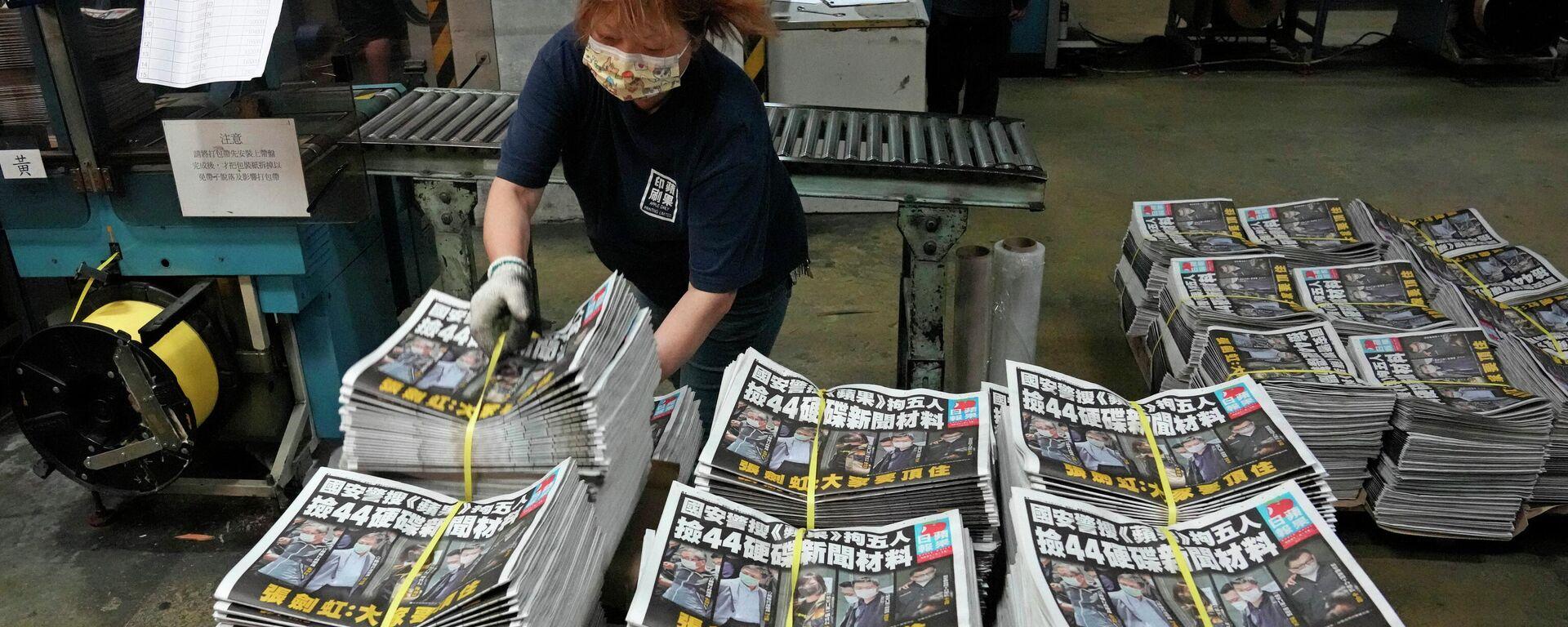 Eine MItarbeiterin einer Druckerei in Hongkong verpackt Exemplare der Zeitung Apple Daily (Archivbild) - SNA, 1920, 21.06.2021