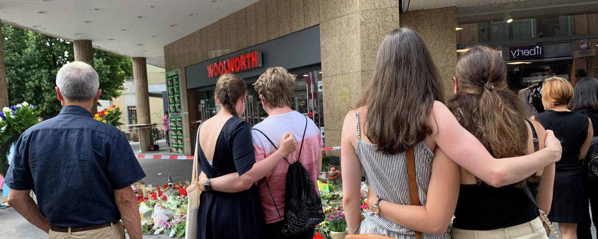 Menschen trauern neben Blumen und Kerzen vor einem Kaufhaus in Würzburg, 27. Juni 2021, nach einem Messerangriff am Freitag durch einen 24-jährigen somalischen Einwanderer, bei dem drei Frauen getötet und fünf weitere Frauen schwer verletzt wurden.  - SNA, 1920, 28.06.2021