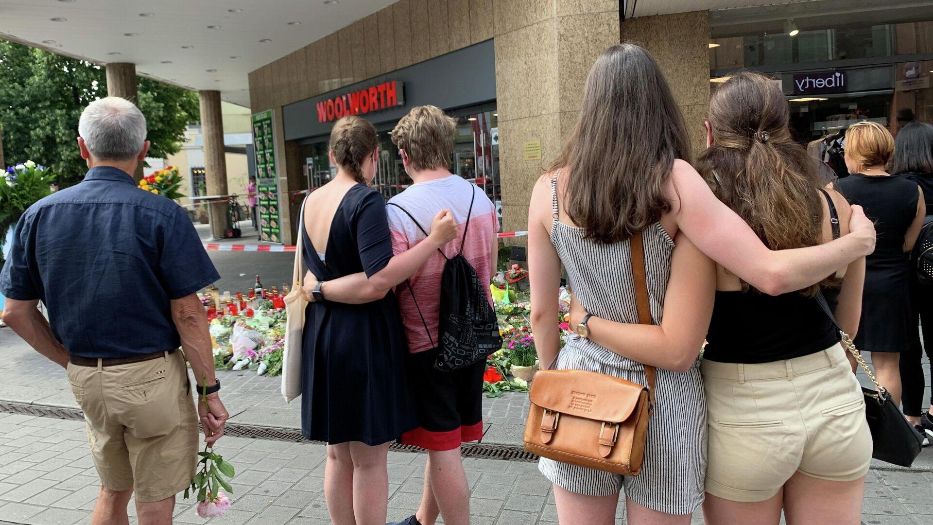 Menschen trauern neben Blumen und Kerzen vor einem Kaufhaus in Würzburg, 27. Juni 2021, nach einem Messerangriff am Freitag durch einen 24-jährigen somalischen Einwanderer, bei dem drei Frauen getötet und fünf weitere Frauen schwer verletzt wurden.  - SNA, 1920, 04.07.2021