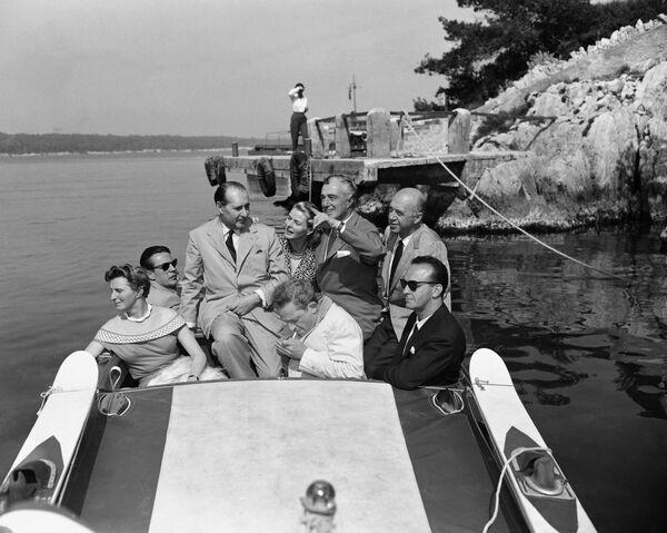 Der italienische Filmemacher Roberto Rossellini und seine Frau, die Schauspielerin Ingrid Bergman (in der Mitte), in einem Schnellboot während der 9. Filmfestspiele in Cannes, 1956. - SNA