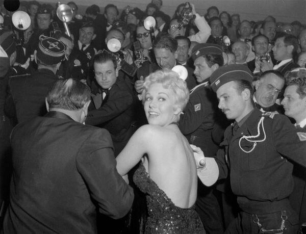 Der US-Star Kim Novak drängt sich durch den Pulk der Fotografen bei den 9. Filmfestspielen von Cannes, 1956. - SNA