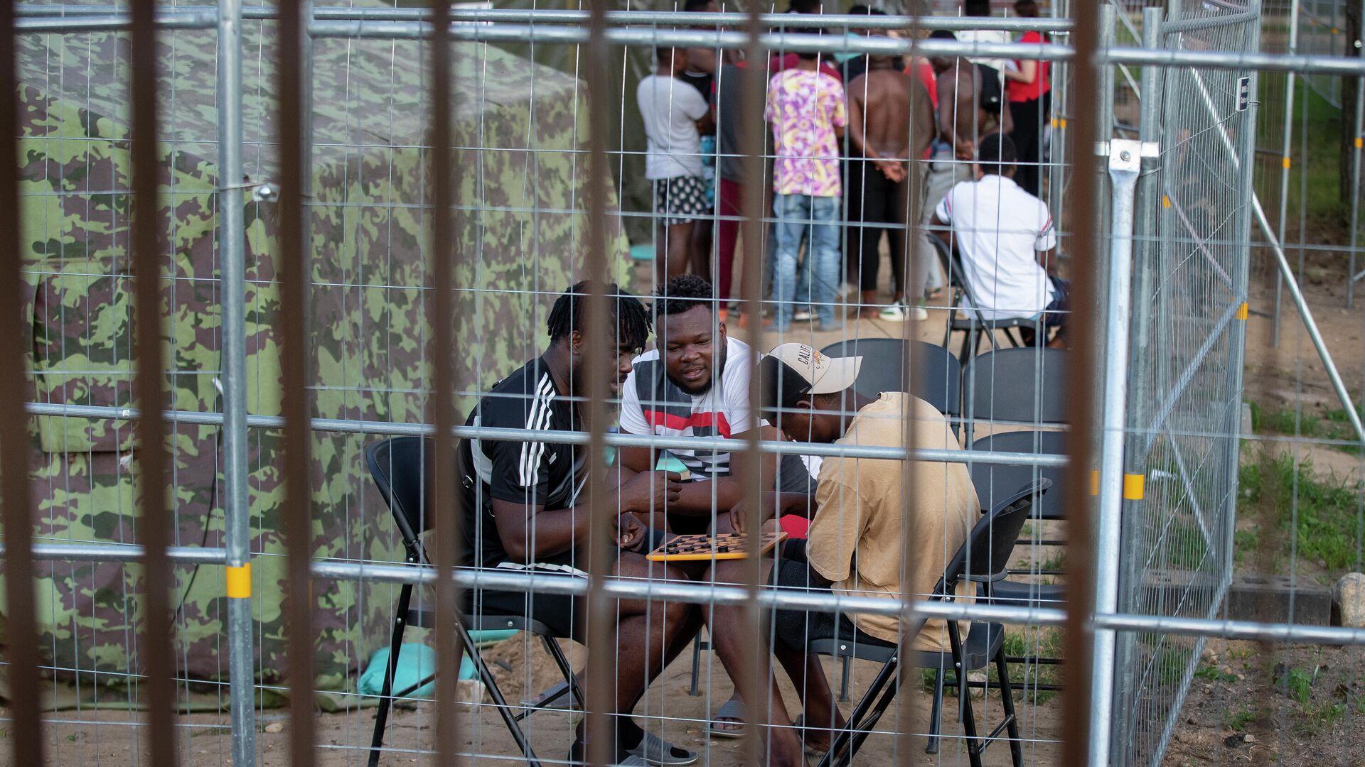 Migranten spielen Dame im neu errichteten Flüchtlingslager in der Stadt Pabrade, Litauen, 8. Juli 2021. - SNA, 1920, 09.07.2021