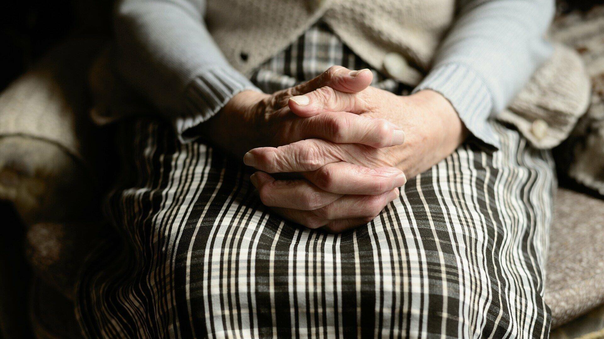 Eine alte Frau sitzend mit ihren Händen auf den Knien (Symbolbild) - SNA, 1920, 11.07.2021