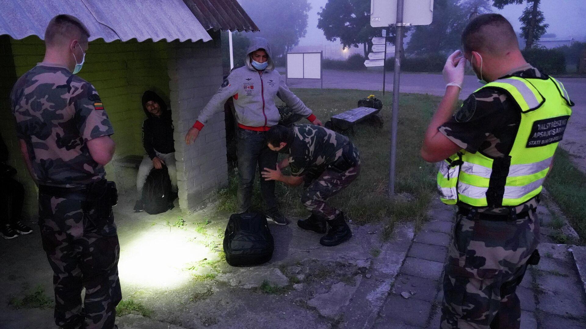 Litauische Grenzschutzbeamten nehmen MIgranten an der Grenze zu Weißrussland fest - SNA, 1920, 12.07.2021
