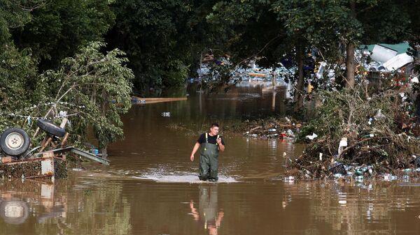 Мужчина идет по затопленному району, пострадавшему от наводнения после проливных дождей, в Бад-Нойенар-Арвайлере, Германия - SNA