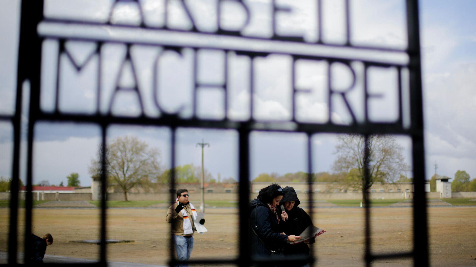 Menschen stehen hinter dem Tor mit der Aufschrift Arbeit macht frei im NS-Todeslager Sachsenhausen (Symbolbild) - SNA, 1920, 09.09.2021