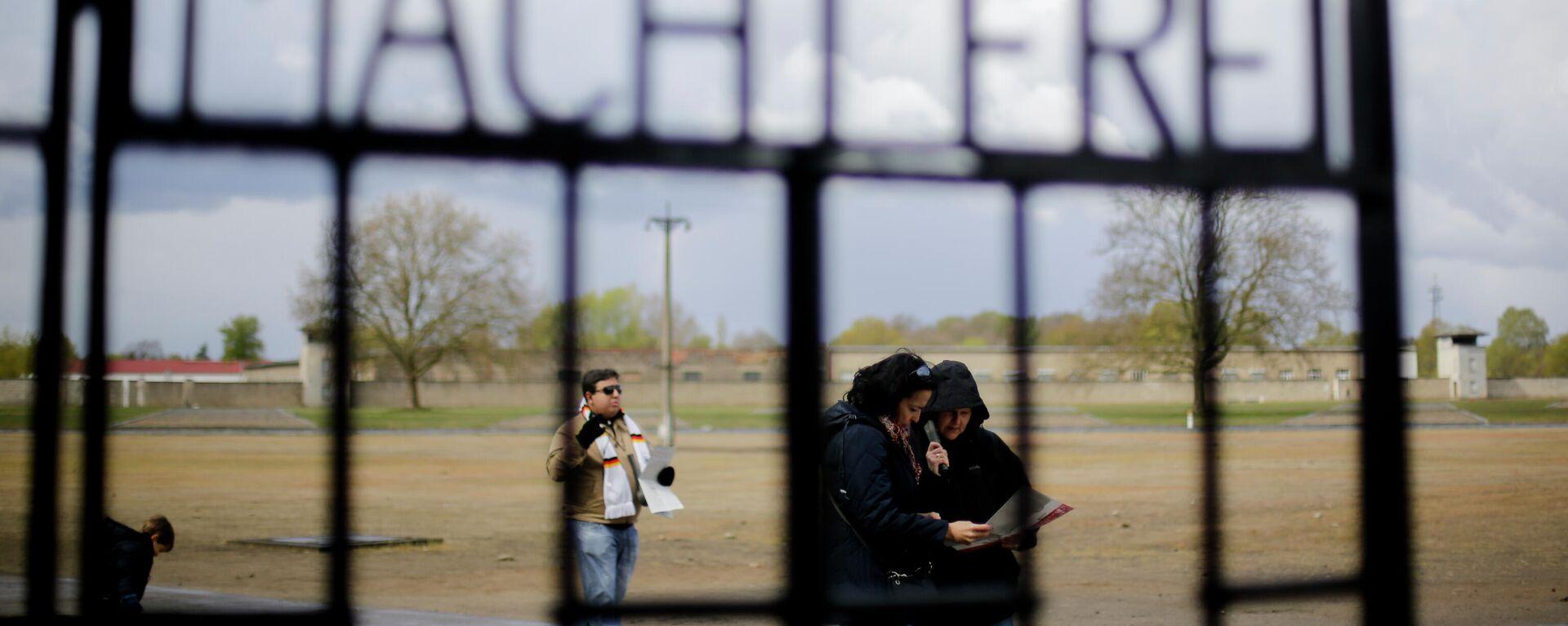Menschen stehen hinter dem Tor mit der Aufschrift Arbeit macht frei im NS-Todeslager Sachsenhausen (Symbolbild) - SNA, 1920, 08.10.2021