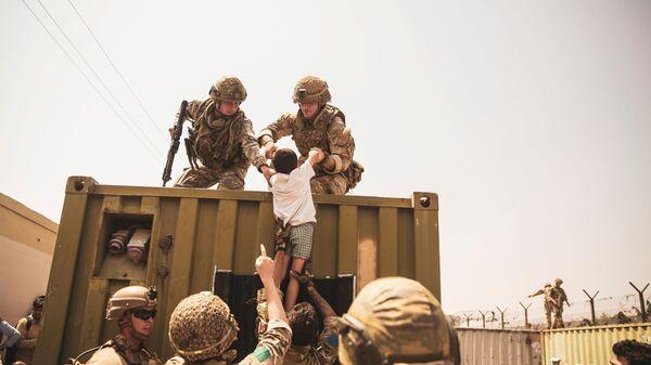 Британские, турецкие и американские солдаты с детьми во время эвакуации в аэропорту Кабула  - SNA