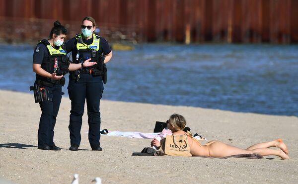 Polizisten sprechen mit einer Frau am Strand in Melbourne. - SNA