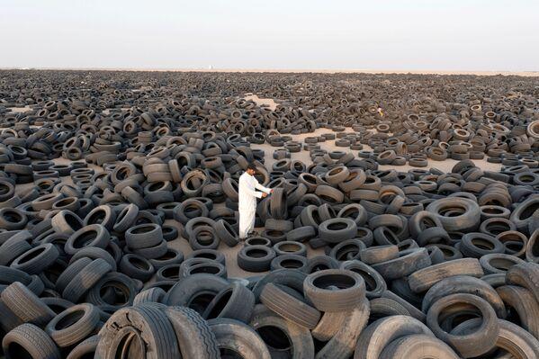 Ein Mann steht unter Autoreifen, die verarbeitet werden sollen, in Kuwait. - SNA