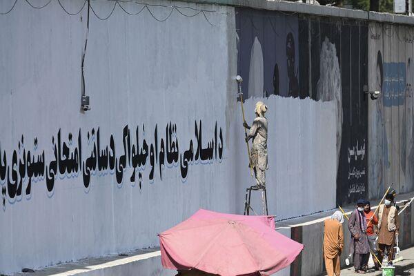 Ein Mann übermalt Graffitis in Kabul. - SNA