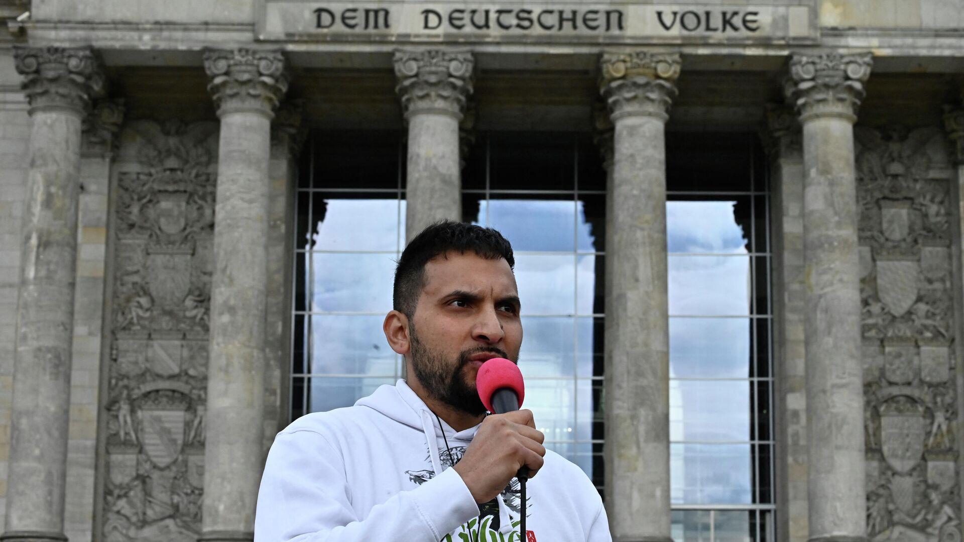 Der deutsche Kochbuchautor und Verschwörungstheoretiker Attila Hildmann  steht vor dem Reichstagsgebäude und spricht während eines Protests gegen die coronabedingten Einschränkungen. 16. Mai, 2020. - SNA, 1920, 13.09.2021