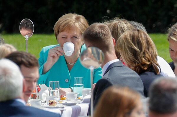 """Die Erfolge der Bundesregierung wirkten sich auch auf die Popularitätswerte der Bundeskanzlerin und der Unionsparteien aus. Das """"Forbes""""-Magazin kürte Merkel zehn Mal in Folge zur mächtigsten Frau der Welt. """"The Times"""" setzte sie zweimal auf die Liste der 100 einflussreichsten Personen der Welt.Foto: Angela Merkel auf einem feierlichen Empfang anlässlich des 70. Jahrestags des deutschen Grundgesetzes im Garten von Schloss Bellevue in Berlin, 2019. - SNA"""