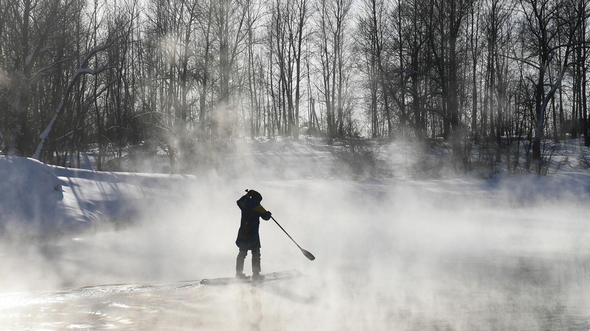 Ein Athlet der SUP-Novosibirsk Sapsurfing-Gruppe beim Winterschwimmen auf einem nicht zugefrorenen Fluss in der Nähe von Novosibirsk - SNA, 1920, 23.09.2021