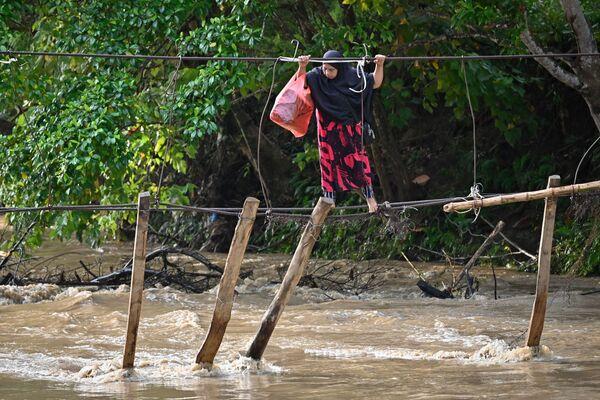 Eine Frau auf dem Rest einer Brücke in Sulawesi, die durch Überschwemmungen vor einem Jahr zerstört wurde. - SNA