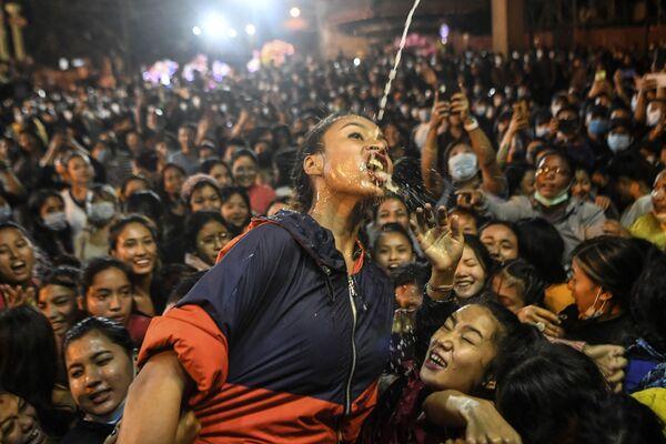"""Gläubige trinken Wein, der aus dem Mund der Statue des Weißen Bhairava fließt, während des """"Indra Jatra""""-Festivals in Kathmandu. - SNA"""