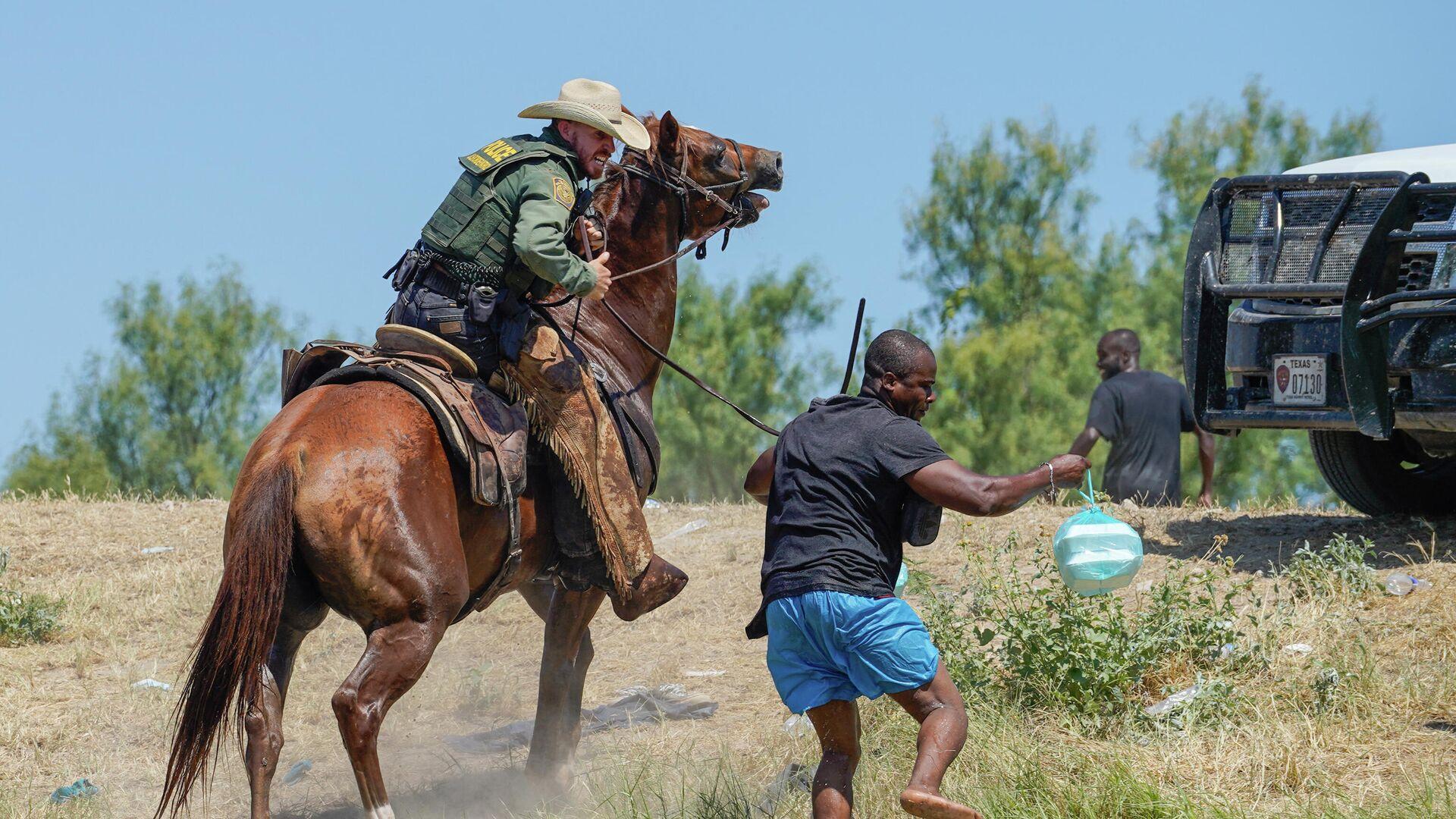 Ein US-Grenzschutzbeamter auf einem Pferd versucht, einen haitianischen Migranten am Betreten eines Lagers am Ufer des Rio Grande zu hindern. - SNA, 1920, 25.09.2021