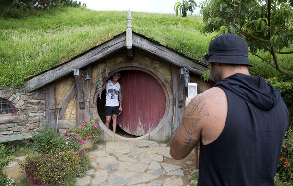 """Touristen lassen sich in einer ehemaligen Farm fotografieren, die zum Dorf Hobbiton für den Film """"Der Hobbit"""" nahe der Stadt Matamata in Neuseeland umgebaut wurde, 2015. - SNA"""