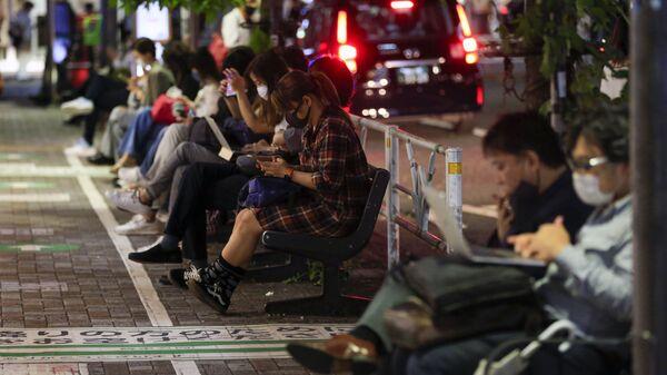 Люди сидят возле железнодорожного вокзала в Токио - SNA
