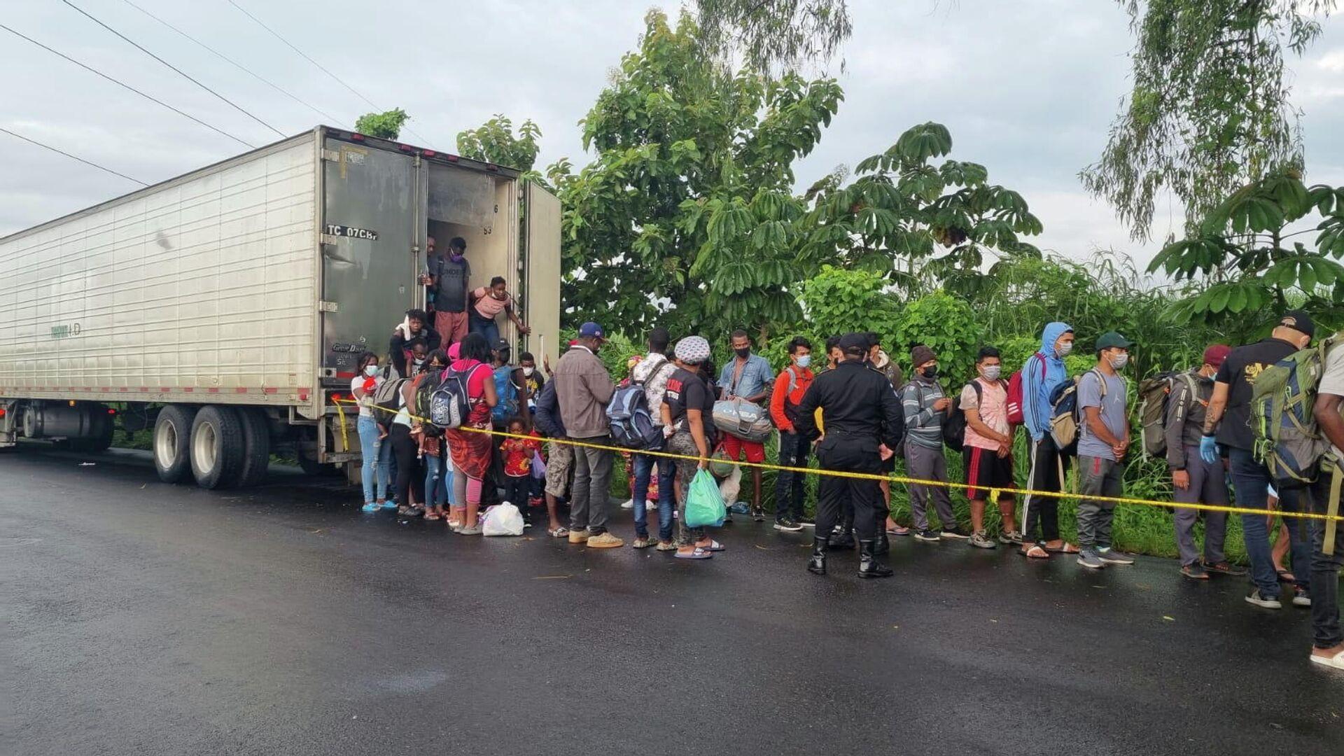 Migranten, die in einem Lastwagen unterwegs sind, steigen aus, nachdem der Lastwagen von der Nationalen Zivilpolizei Guatemalas (PNC) in Mazatenango, Guatemala, angehalten wurde (undatiertes Foto). - SNA, 1920, 10.10.2021