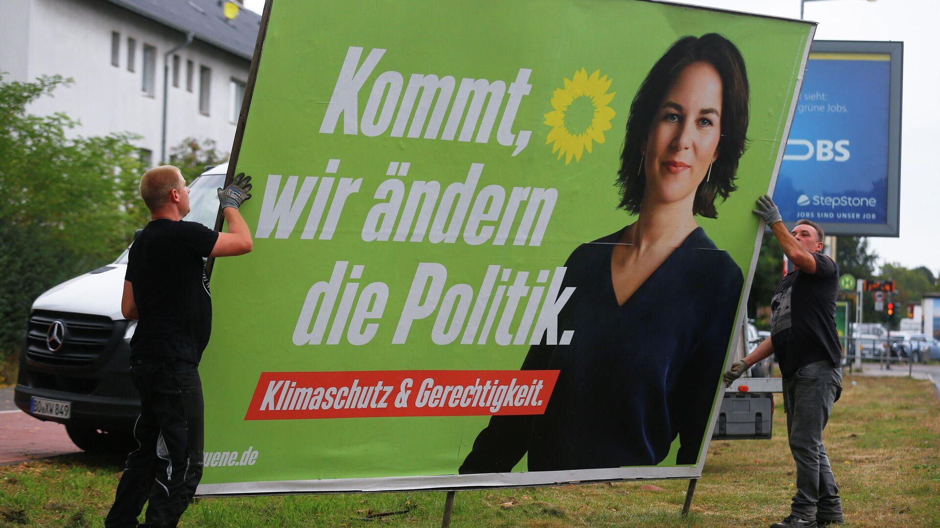 Arbeiter entfernen ein Wahlplakat mit der Grünen-Kanzlerkandidatin Annalena Baerbock - SNA, 1920, 14.10.2021