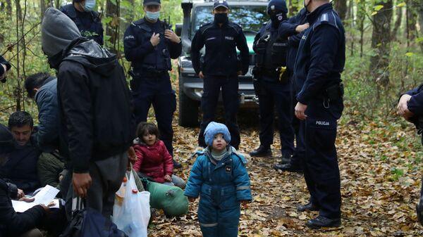 Мигранты в окружении пограничников и полицейских после того, как они пересекли белорусско-польскую границу, Хайновка, Польша - SNA