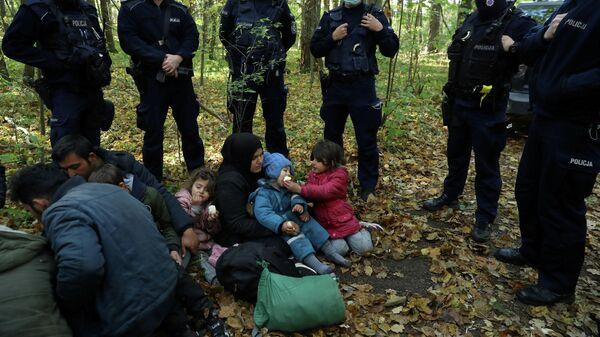 Eine irakische Migrantin mit Kindern sitzt auf dem Boden an der polnischen Grenze in Hajnowka, am 14. Oktober 2021. - SNA